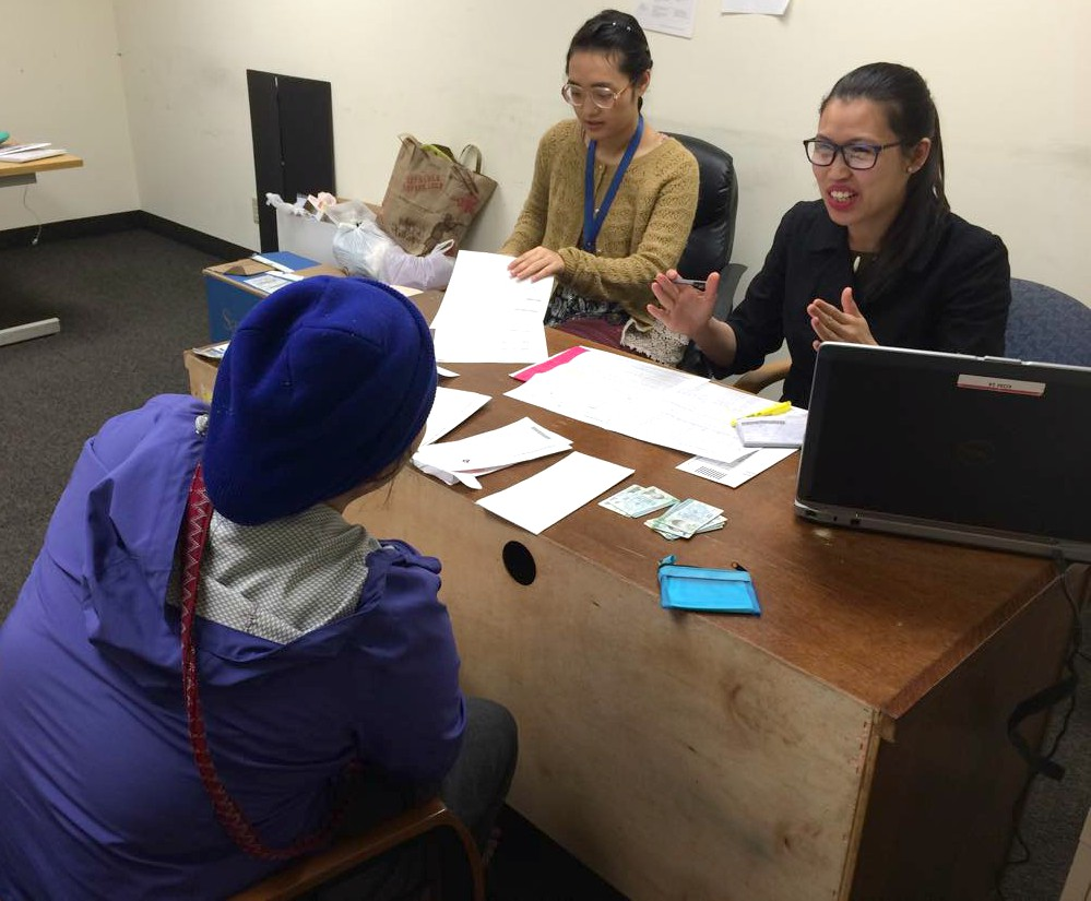 Bway Khu (in black) helps a walk-in client while training another volunteer in human services.