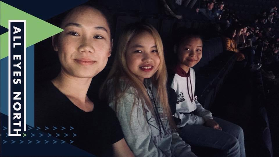 Youth Mentor, Ehywa Htoo, sits with her two mentees at a Timberwolves game in April.