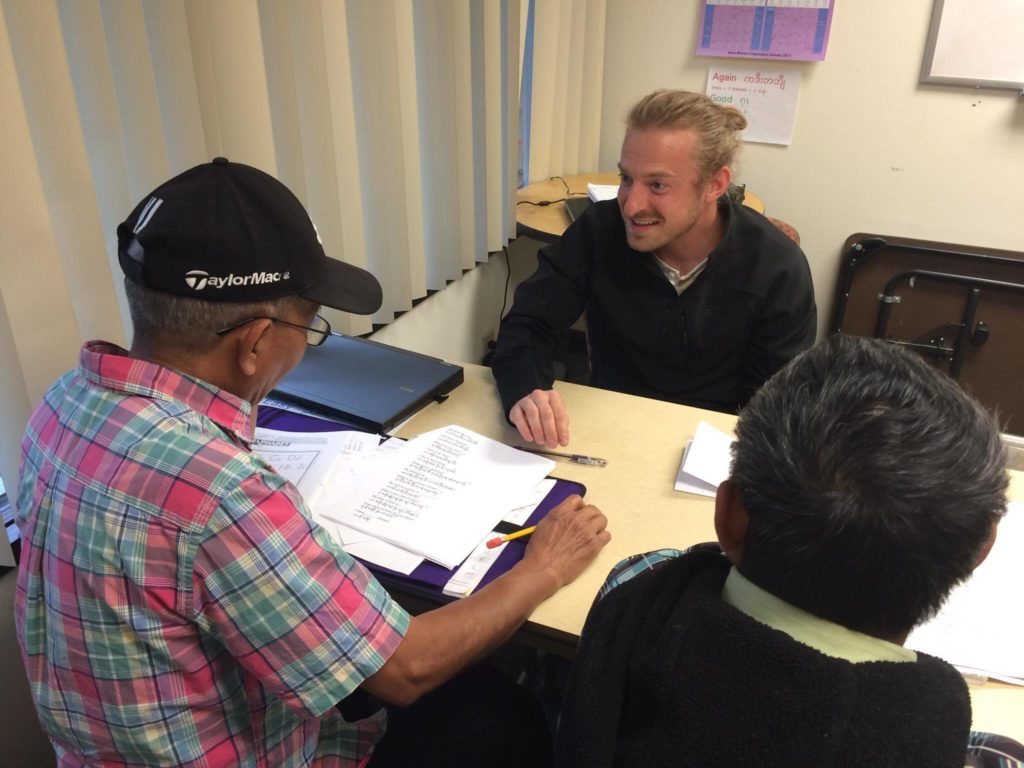 ESL Tutor, Jonathan, helps students in small groups on their assignments