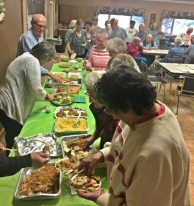 Seniors at the Adult Community Center dish up a variety of good food