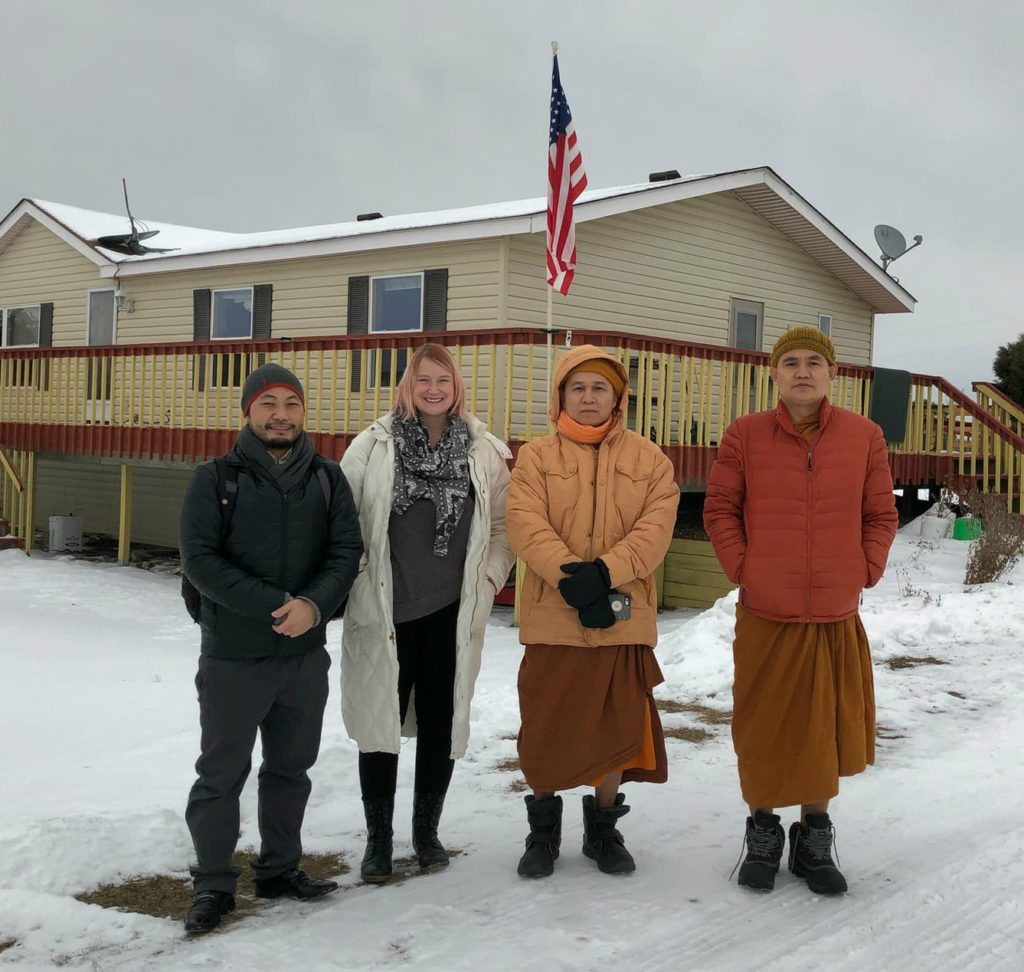 Ner Mu and Jennifer Plum meeting with Karen Buddhist monks in the winter at a Buddhist temple in MN
