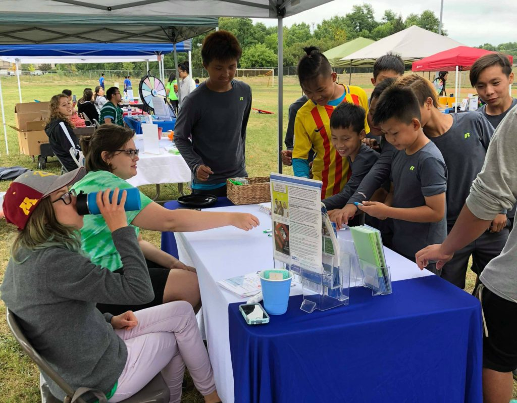 A Karen boys soccer team visits an info booth about raising the legal tobacco age to 21