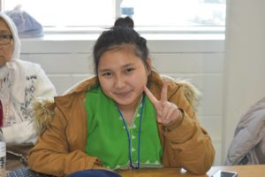 A Karen girl looks at the camera and makes a peace sign.