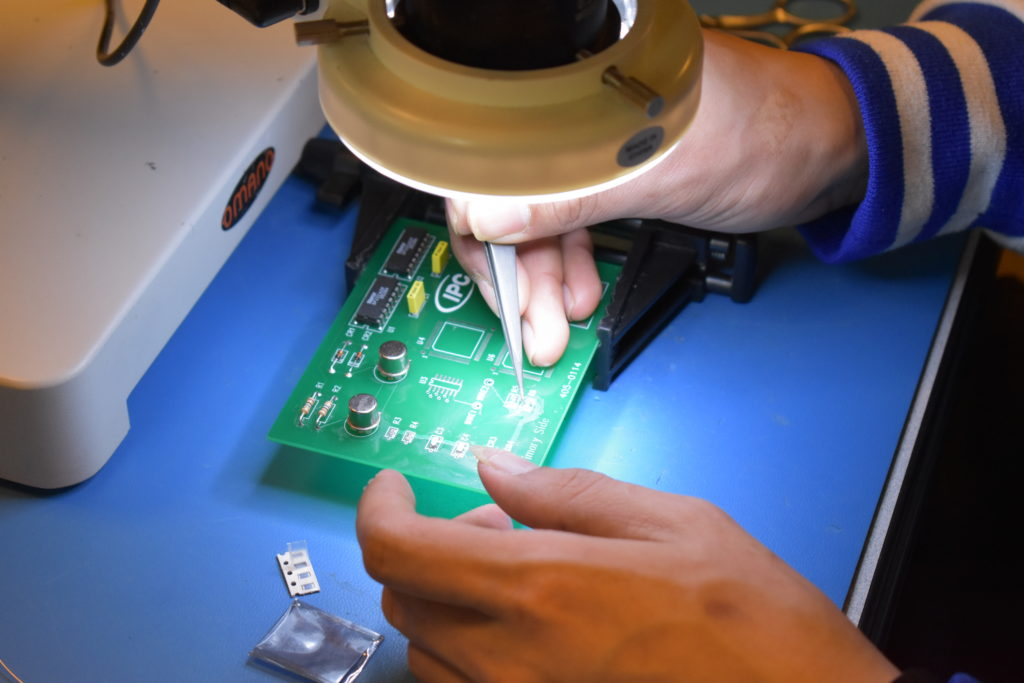 A participant working on a soldering board