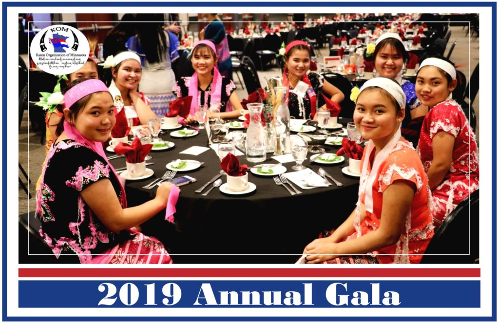 Image of Karen youth dance group seated at a dining table at the 2018 annual gala. They are wearing traditional Karen dress and looking at the camera.